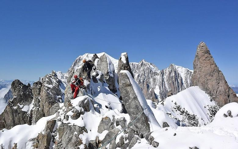 Traversing the summit of the Aiguille du Rochefort via the Rochefort arete with the Dent du Geant and Mont Blanc in the background